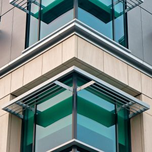 Corner of a modern building with green glass, stone facade, and aluminum awnings.